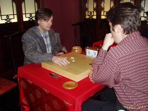 В Го, как и в жизни борятся случайность, воля и фатум. Один из элементов случайности - миниигра перед главным сражением. Определение цвета: нигири. Играть белыми против Дмитриева крайне сложно...