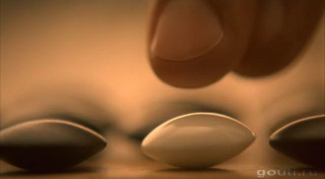 Видно как рука ставит камень